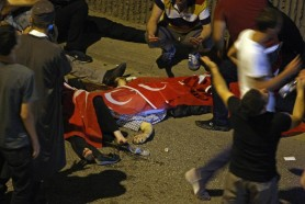 People react as bodies draped in Turkish flags are seen on the ground during an attempted coup in Ankara